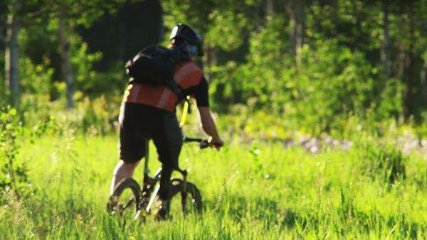 Medium shot pan of Rear view of man with artificial limb riding mountain bike through meadow, American Fork Canyon, Utah Royalty-free stock video