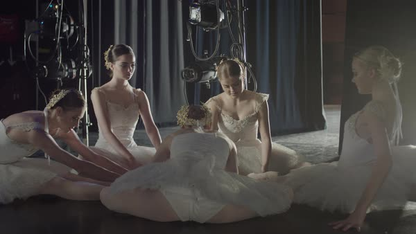 Medium slow motion panning shot of ballerinas stretching backstage Rights-managed stock video