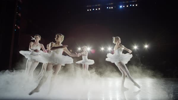Wide slow motion panning shot of ballerinas dancing in fog Rights-managed stock video