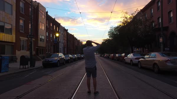 Wide shot of a man taking photographs in a suburb of Philadelphia Royalty-free stock video
