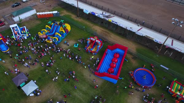 An Aerial Shot Of People And Families Playing At A Small Fair With Rides Food