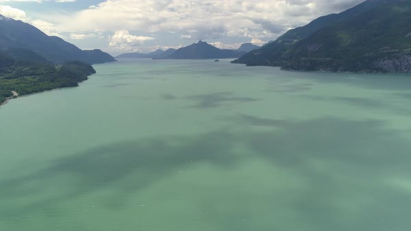 Aerial Ocean Pan to Turquoise Water and Islands of Thick Forest Mountains on Howe Sound Royalty-free stock video