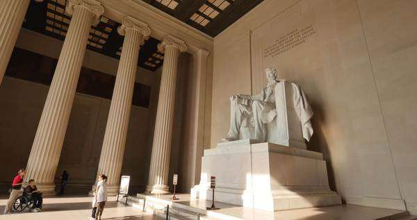 WASHINGTON, D.C. - July, 2015 - An interior establishing shot of the Lincoln Memorial as tourists view the statue of a sitting Abraham Lincoln. Royalty-free stock video