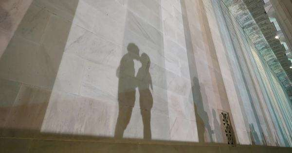 Two lovers kiss at the base of the Lincoln Memorial at night while their shadows fall on the marble walls. Royalty-free stock video