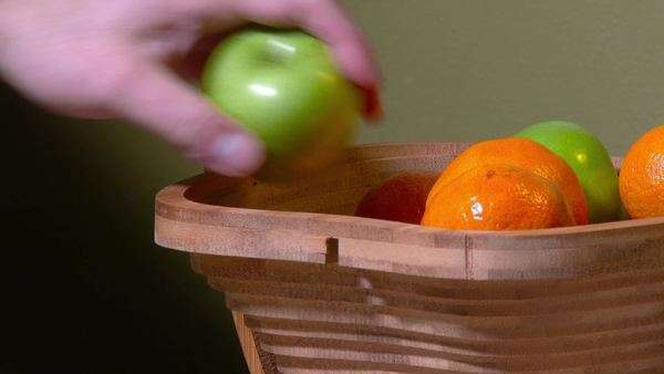 A hand reaches into a fruit basket and takes an apple. Royalty-free stock video
