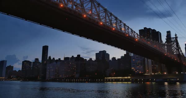 An evening or dusk establishing shot of the Manhattan skyline as seen from under the Ed Koch Queensboro Bridge.  	 Royalty-free stock video