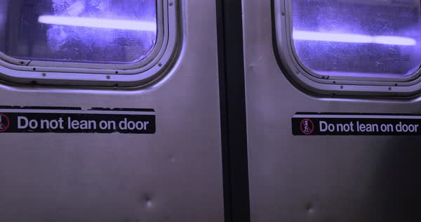 A close-up shot of the closed doors on a moving New York City subway car.  	 Royalty-free stock video