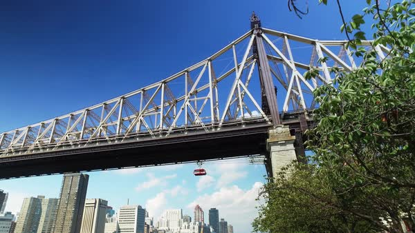 A low angle daytime establishing shot of the Ed Koch Queensboro Bridge with the Roosevelt Island Tram traveling beside.  	 Royalty-free stock video
