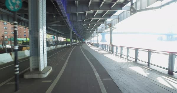 A bicycle rider's perspective on the East River Bikeway trail underneath FDR Drive in Manhattan.  	 Royalty-free stock video