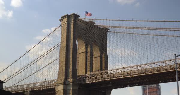 A dramatic low angle view from under the Brooklyn Bridge on a summer day.  Royalty-free stock video
