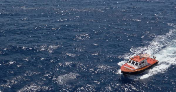 A wide shot of a small pilot ship cutting through the ocean waters. Royalty-free stock video