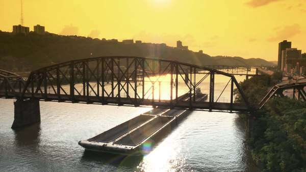 An empty coal barge travels up the Monongahela River near Pittsburgh, PA at dusk. Royalty-free stock video