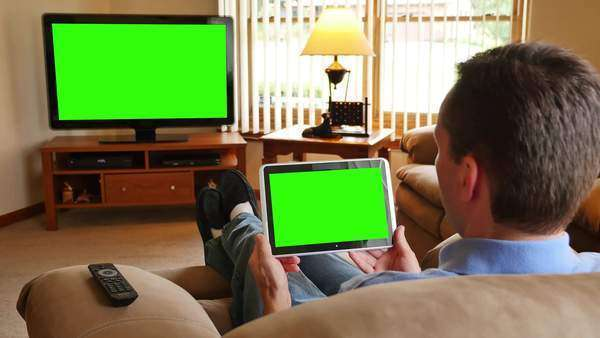 A man watches television while holding a and tapping on a tablet device. Royalty-free stock video