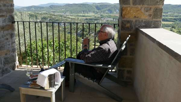A man relaxes on a balcony with a glass of wine in a village in the Spanish Pyrenees Royalty-free stock video