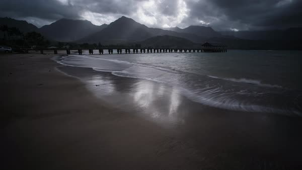 Kauai timelapse, Hanalei pier with dramatic light rays and ocean waves. Rights-managed stock video