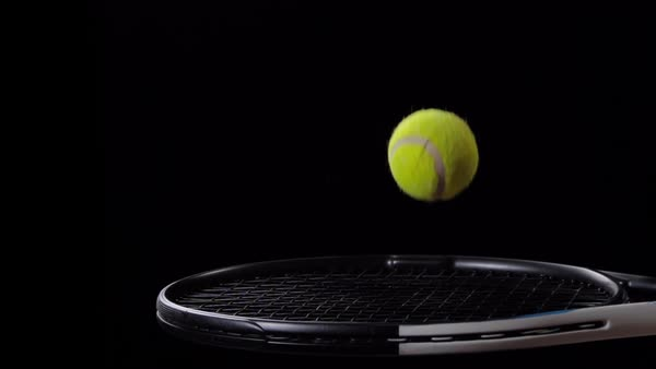 Tennis Ball Bounces On Racket Slow Motion Black Background Stock