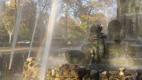 Brooklyn, New York City: Zoom in on Neptune statue at Bailey Fountain, with girl sitting in the morning sun on a nearby bench Royalty-free stock video
