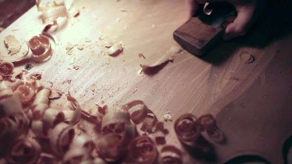 Close-up shot of a violin maker planing a piece of wood Royalty-free stock video
