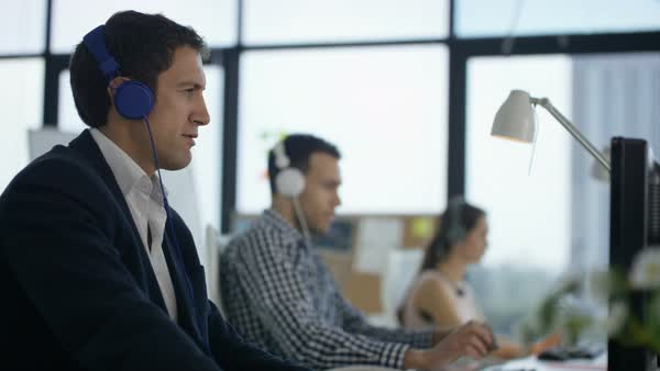 Happy workers in office working & listening to music through headphones  stock footage