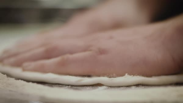 Hand-held shot of a person stretching out dough in flour Royalty-free stock video