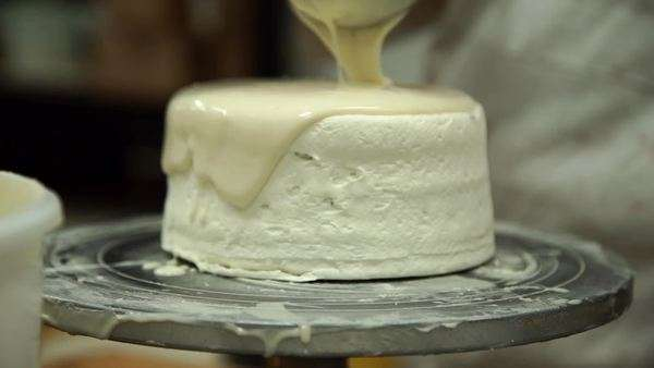 Slow motion of a baker pouring icing on a cake Royalty-free stock video
