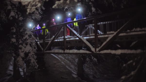 Wide-angle shot of hikers crossing a bridge in Johnston Canyon at night Royalty-free stock video
