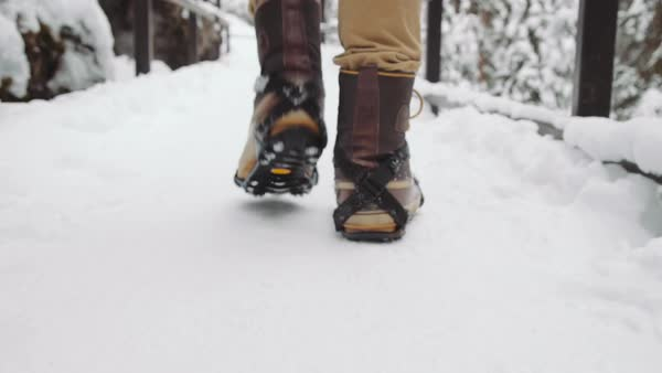 Close-up shot of a person walking on a snowy bridge in Johnston Canyon Royalty-free stock video