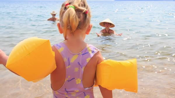 52bd9fbd67 Close-up little girl with pigtail in yellow safety armbands goes to mother  in hat in transparent azure sea - Stock Video Footage - Dissolve