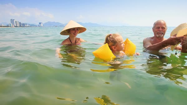 ed376ebfed Little girl in yellow safety armbands swims from mother in hat to grandpa  in transparent sea - Stock Video Footage - Dissolve