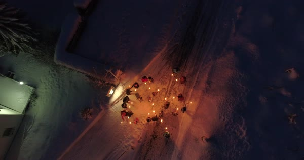 Drone shot of people standing on a snowy road with torches Royalty-free stock video