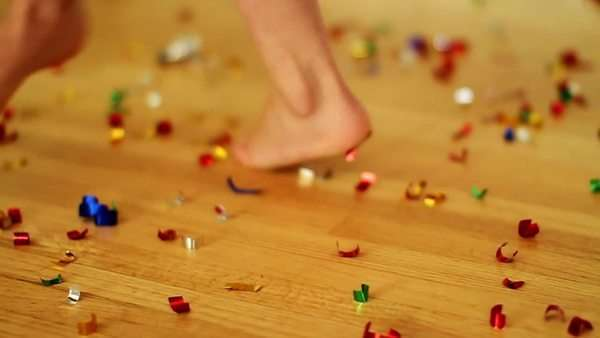 Close up of a little girl's feet as she is dancing in circles as confetti lies all over the floor Royalty-free stock video
