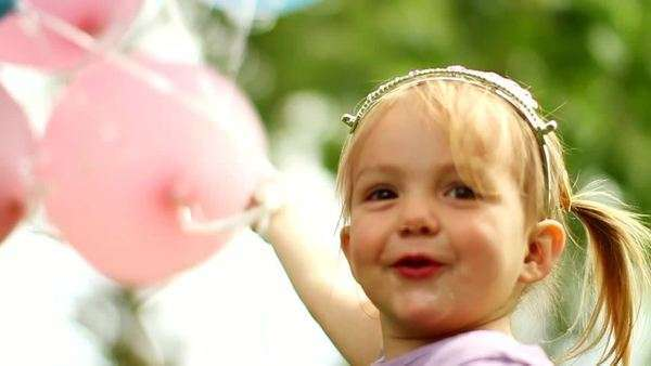 Close-up of a happy little girl holding a bunch of balloons outside Royalty-free stock video