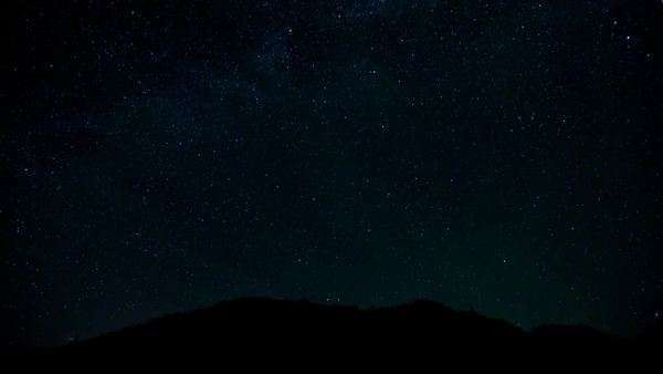 Night timelapse of star movement over Jelm Mountain near Woods Landing, Wyoming Throughout the timelapse clouds form and the moon rises Royalty-free stock video