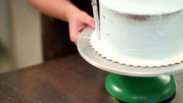 Professional baker spreads icing evenly over cake Royalty-free stock video