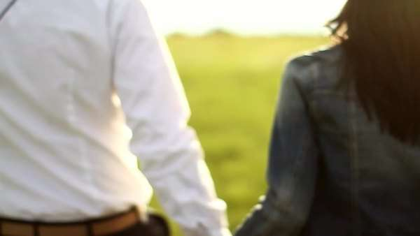 Young adult couple walking through field on a romantic date Royalty-free stock video