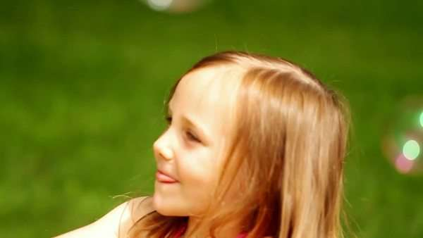 Little girl chasing and popping bubbles Royalty-free stock video