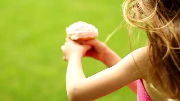 Little girl running through field with cupcake Royalty-free stock video