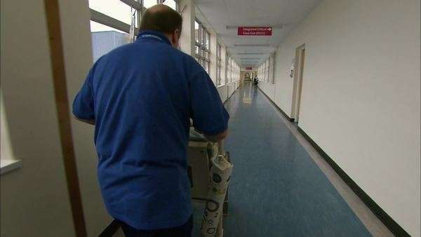 Porter moving patient in wheelchair in hospital corridor. Royalty-free stock video