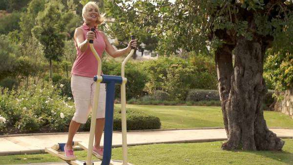 Senior woman using exercise machine in park. Royalty-free stock video