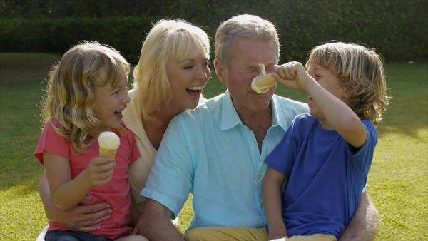 Grandparents and grandchildren sitting together in garden playing with ice cream. Royalty-free stock video