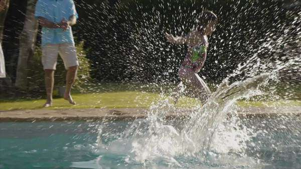 Slow motion of grandchildren jumping into swimming pool in garden. Royalty-free stock video