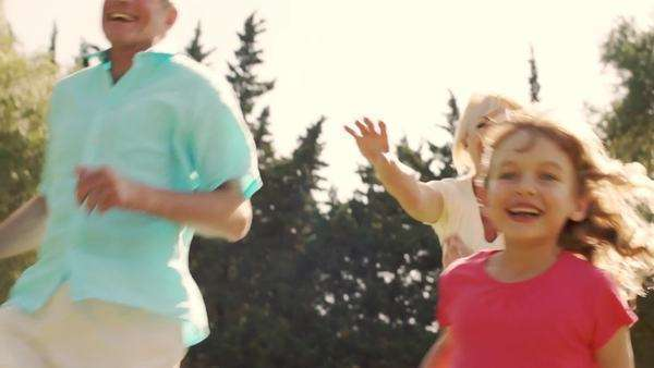 Dolly shot of grandparents and grandchildren running together in garden. Royalty-free stock video