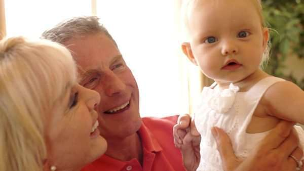 Grandparents and baby granddaughter playing on sofa indoors. Royalty-free stock video