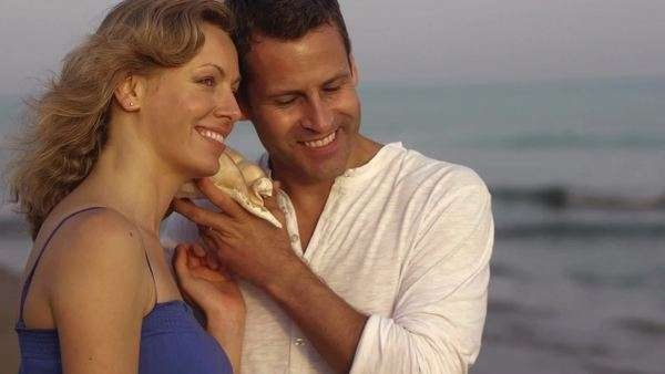 Couple listening to conch shell by sea. Royalty-free stock video
