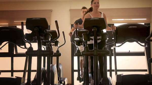 Dolly shot of couple at gym exercising on cross trainer. Royalty-free stock video