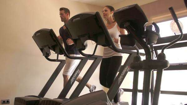 Dolly shot of couple running on treadmill at gym. Royalty-free stock video