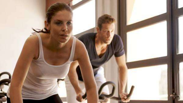Dolly shot of young couple on exercise bikes at gym. Royalty-free stock video
