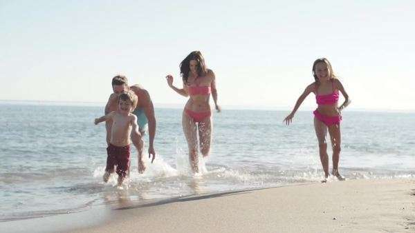 Slow motion of family running out of the sea. Royalty-free stock video