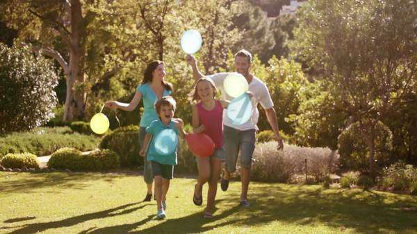 Slow motion of family in park running with balloons. Royalty-free stock video