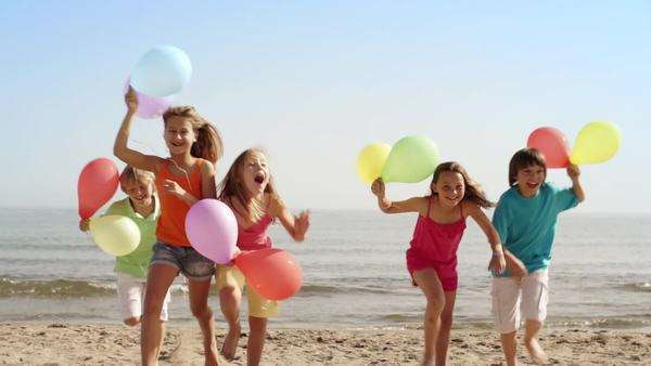 Slow motion of five children running towards camera on beach holding balloons. Royalty-free stock video